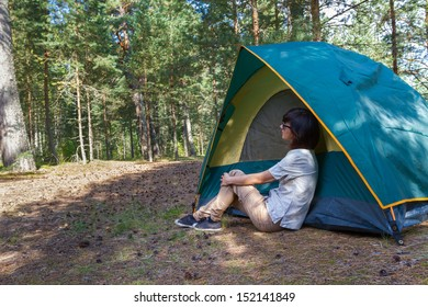 Young woman in front of camp tent against forest