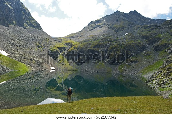 Young woman in front of high mountain peaks and lake