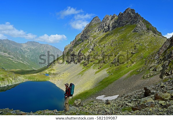 Young woman in front of high mountain peak and blue lake