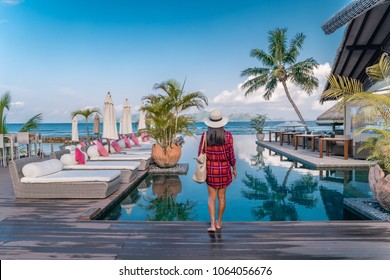 young woman in front of an Luxury infinity swimming pool looking out over the ocean, relaxing holidays in Seychelles islands. La Digue