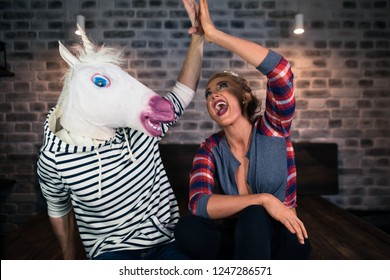 Young woman with funny man in comical mask sits in stylish room. Unusual happy couple. Blonde girl give five to boyfriend in modern apartments.