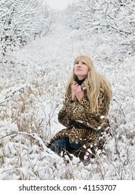 young woman in fur coat outdoors in snow garden