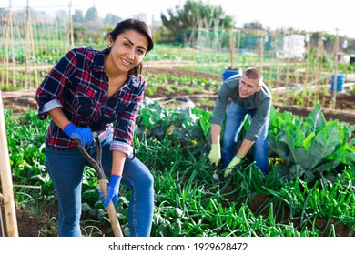 Young woman gardener holding shovel in garden against background of working people
