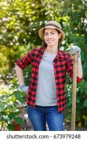young woman gardener holding spade in garden. Hobby concept