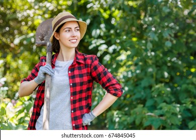 young woman gardener holding spade in garden. Copy space. Hobby concept