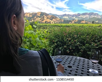 Young woman gazing over Napa Valley vineyards while holding glass of red wine on table