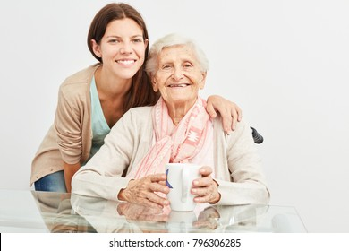 Young woman as a geriatric nurse assisting a senior citizen in a retirement home