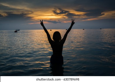 The young woman gestures with two fingers to cheer in the middle of the sea in the evening of a lonely day.