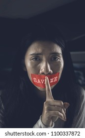 Young woman gesturing silence while sitting in the dark room with her mouth covered by text of Save Me on a red tape