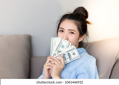 Young woman get first salary of her life. Pretty girl feels proud of her self that she can earn a lot of money. Beautiful woman holds dollar, note bank, USA money. Charming beautiful girl feels happy