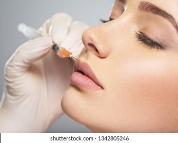 young woman gets botox injection in her lips. Woman in beauty salon. plastic surgery clinic.