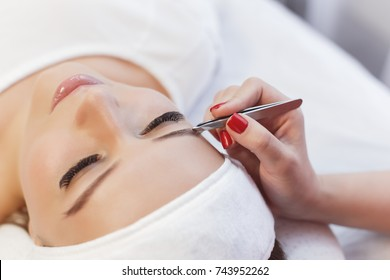 Young woman gets eyebrow correction procedure.Beautiful young girl correction of eyebrows in a salon.professional care for face.