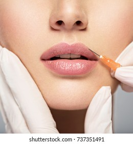 young woman gets injection of botox in her lips. Woman in beauty salon. plastic surgery clinic.