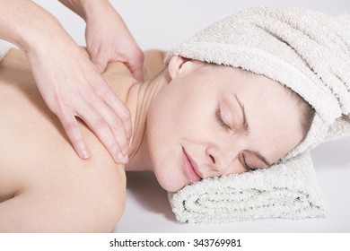 A young woman getting a back massage at a spa