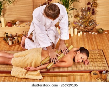 Young woman getting bamboo massage. Male therapist. Two people.