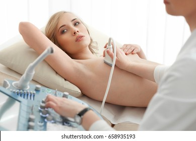 Young woman getting breast examination by her gynecologist ultrasound scanning sonography technology medical equipment healthcare.