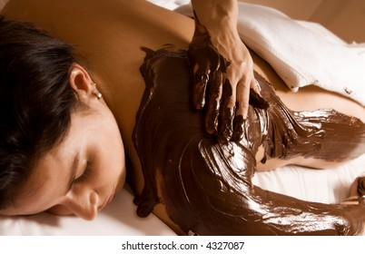young woman getting a chocolate massage at a spa
