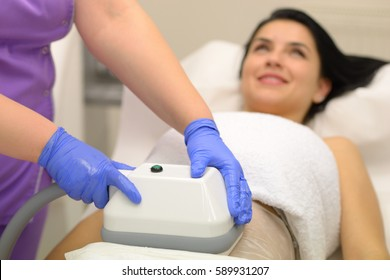 young woman getting cryolipolyse treatment in cosmetic cabinet