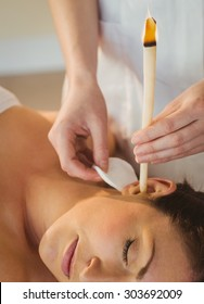 Young woman getting an ear candling treatment in therapy room