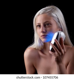 Young woman getting face phototherapy treatment by blue light