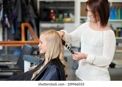 Young woman getting her curled by a stylist at hair salon