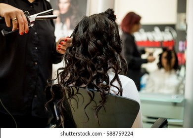 Young woman getting her hair curled by a stylist at a beauty salon. Close up of stylist's hand using curling iron for hair curls
