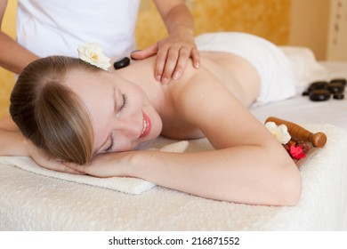 Young woman getting hot stone massage