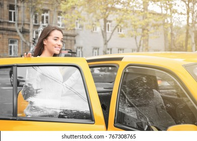 Young woman getting into taxi car