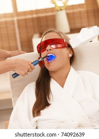 Young woman getting laser tooth whitening treatment at spa.
