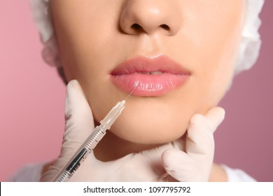Young woman getting lip injection on color background, closeup
