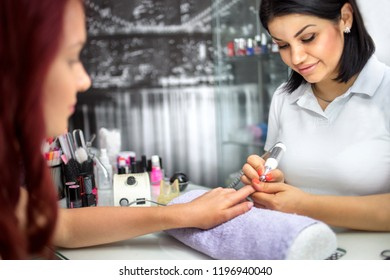 Young woman is getting manicure in beauty salon