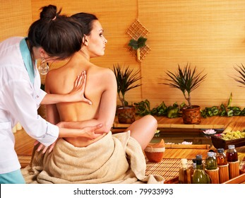 Young woman getting massage in bamboo spa..