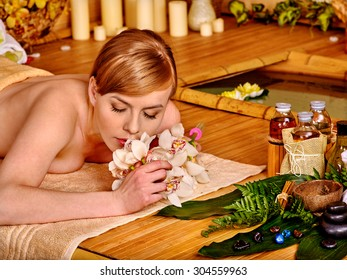 Young woman getting massage in luxury  spa. Girl inhales fragrance of flowers