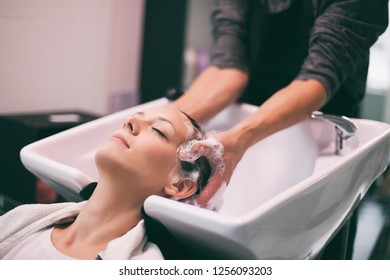 Young woman getting new hairstyle at professional hair styling saloon. Hairdresser is massaging her head.