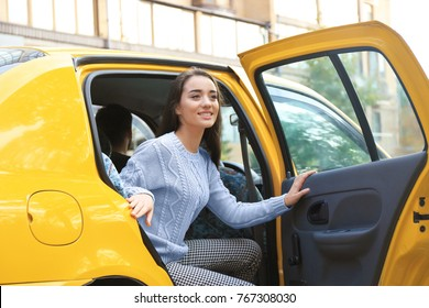Young woman getting out of taxi car