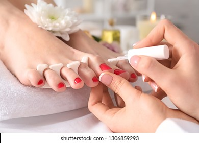 Young woman getting pedicure in beauty salon