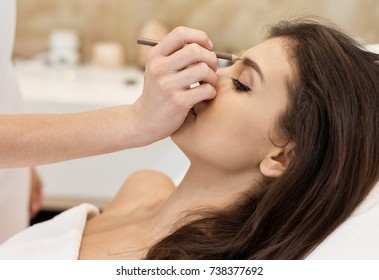 Young woman getting professional makeup from makeup artist.