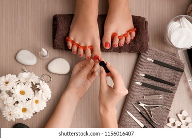 Young woman getting professional pedicure in beauty salon