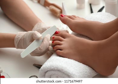 Young woman getting professional pedicure in beauty salon, closeup