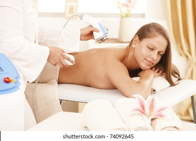 Young woman getting radio frequency fat reduction treatment in day spa.