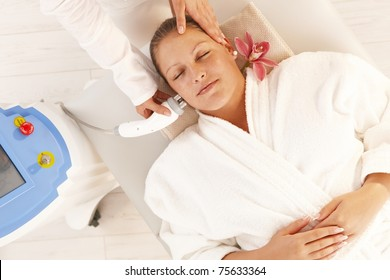 Young woman getting radio frequency fat reduction treatment in day spa, smiling.?