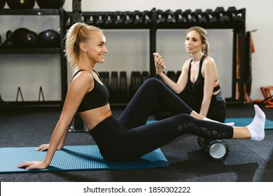 Young woman getting ready for a workout using a sports fascia massage roller to warm up the calf muscles. Another woman resting after training in the background