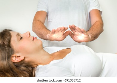 Young woman getting reiki healing therapy - alternative medicine concept