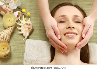 Young woman getting spa massage on bamboo mat. Top view