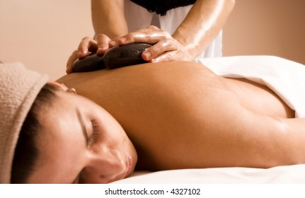 young woman getting a stone massage at a spa