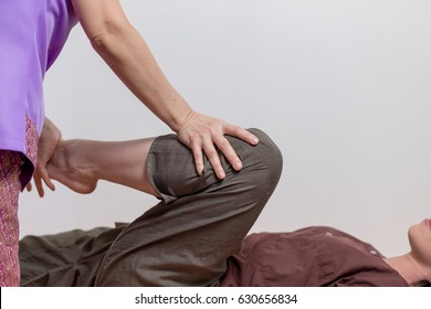 Young woman getting traditional thai stretching massage by asian therapist