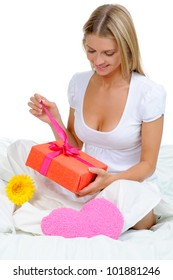 young woman with a gift box in the bed. Isolated on white background
