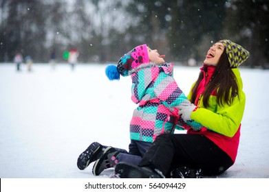 Young woman and the girl in bright ski suits sit having embraced on snow. It is snowing. Mother and daughter language catch snowflakes. They are very much pleased by winter and snow.