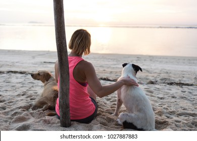 young woman or girl caressing two dogs, wearing sport clothing, enjoying her time and vaction. sunny beach or coast near sea or ocean as background