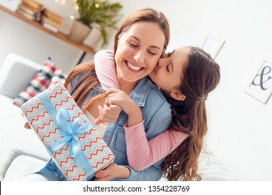 Young woman and girl at home celebrating mother's day sitting on sofa daughter hugging mom holding present box kissing cheek closed eyes pleasure close-up.